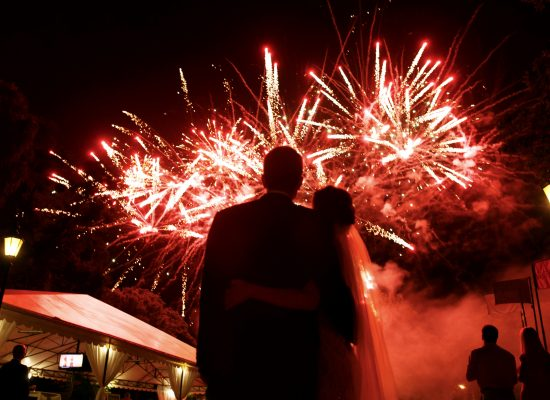 Happy hugging bride and groom watching beautiful colorful fireworks night sky during a NJ wedding fireworks show.