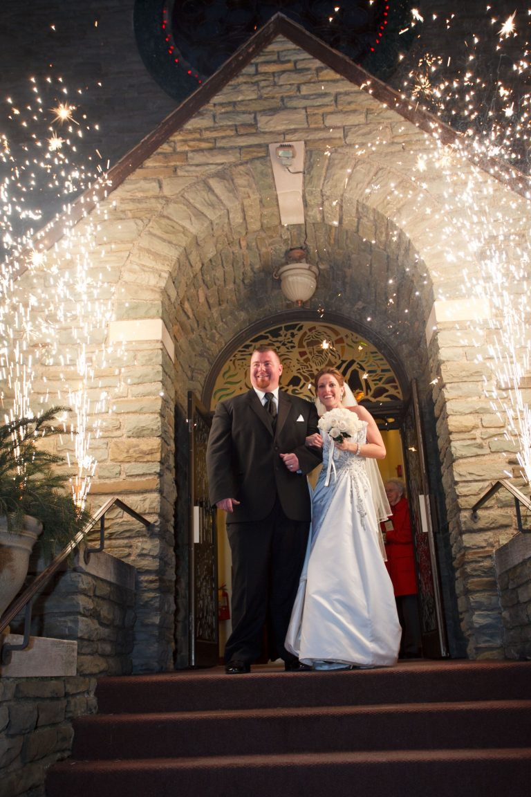 a bride and groom exit a church and walk through close proximate fireworks.