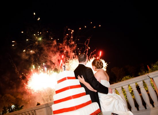 A bride and groom stand next to their wedding cake as a wedding fireworks show goes off.