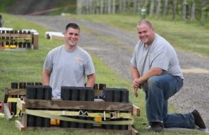 Employees from a nj fireworks company smiling while setting up a fireworks show.