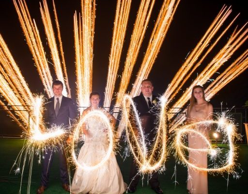 A wedding party spells out LOVE whil fireworks go off in the background for a wedding fireworks show.