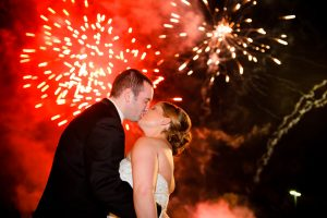 A NJ Wedding Fireworks display with a bride and groom kissing and fireworks going off in the background.