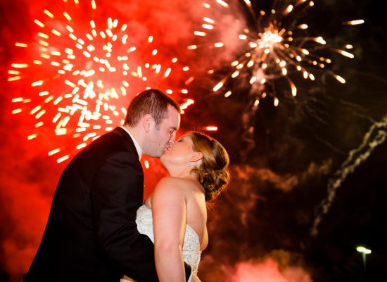 A NJ Wedding Fireworks show with a bride and groom kissing and fireworks going off in the background.