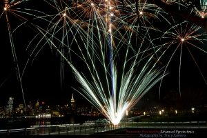 A silver fan cake firework display going off on a pier on the Hudson River with New York City in the background.