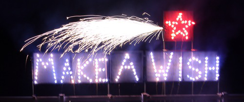 A fire writing set piece for make a wish foundation is displayed and was constructed by a fireworks company.